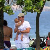 Marcelo Serrado brinca com um de seus filhos gêmeos em parquinho na praia