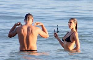 Fernanda Lima e Rodrigo Hilbert trocam carinhos apaixonados no mar do Leblon