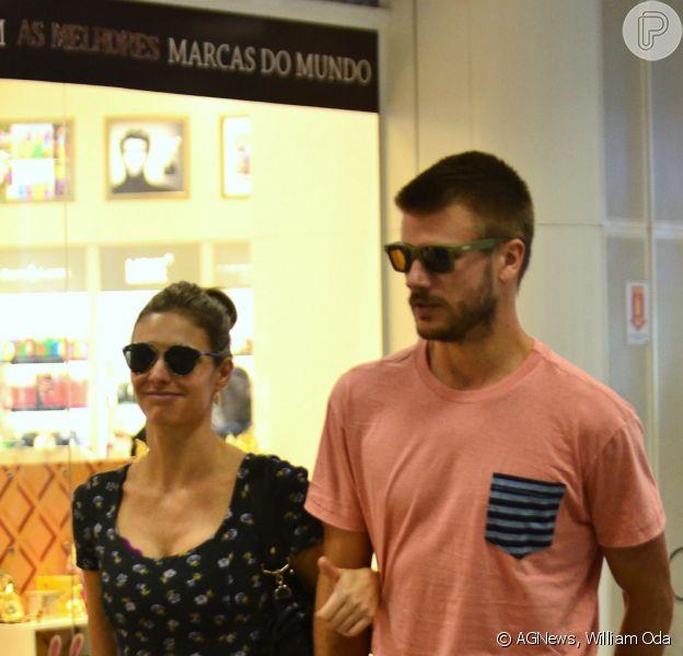 Fernanda Lima acena para fotógrafo ao lado de seu marido, Rodrigo Hilbert