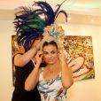 Laryssa Dias experimenta parte da fantasia do Carnaval durante visita ao barracão da Grande Rio, na zona portuária do Rio de Janeiro, em 24 de janeiro de 2013