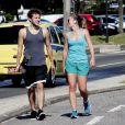 O filho de Jayme Monjardim carrega seu skate enquanto anda com a namorada