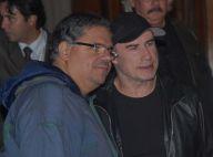 John Travolta atende fãs na porta do hotel onde está hospedado em São Paulo