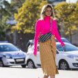 A saia midi mais sóbria pode aparecer combinando com blusas descoladas, como a neon, para um look de verão