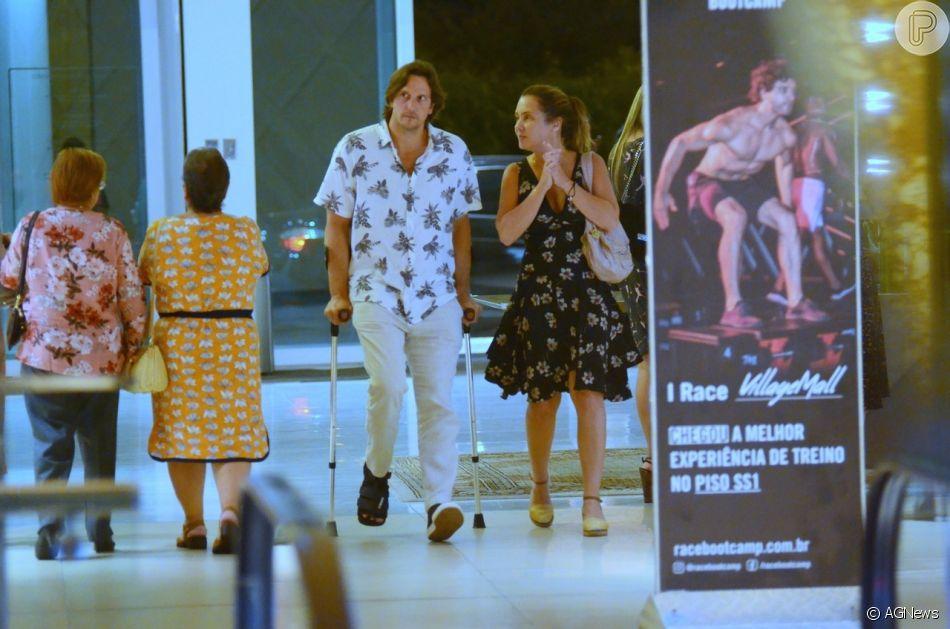 Vladimir Brichta usou muletas e bota ortopédica ao passear em shopping com a mulher, Adriana Esteves, neste sábado, 16 de fevereiro de 2019
