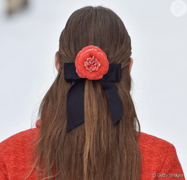 Laço de fita e flor da mesma cor que a roupa estilizavam os looks das modelos da Chanel