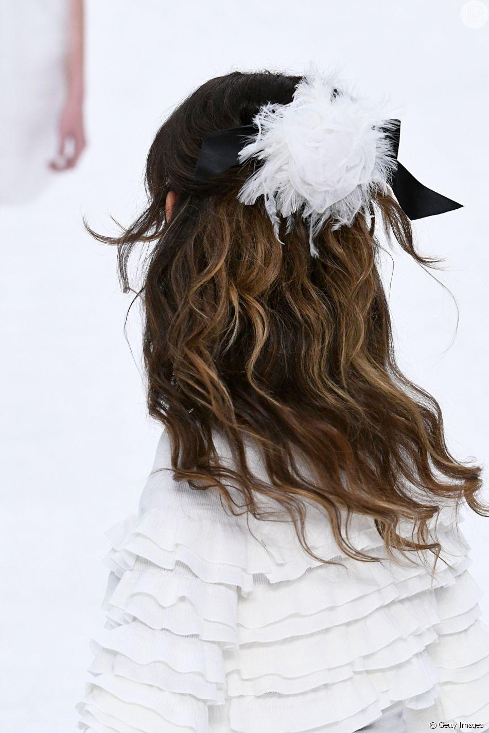 6a97be9c268 A presilha com tule e plumas brancas presa junto ao laço de fita preto foi  destaque nos cabelos das modelos da Chanel