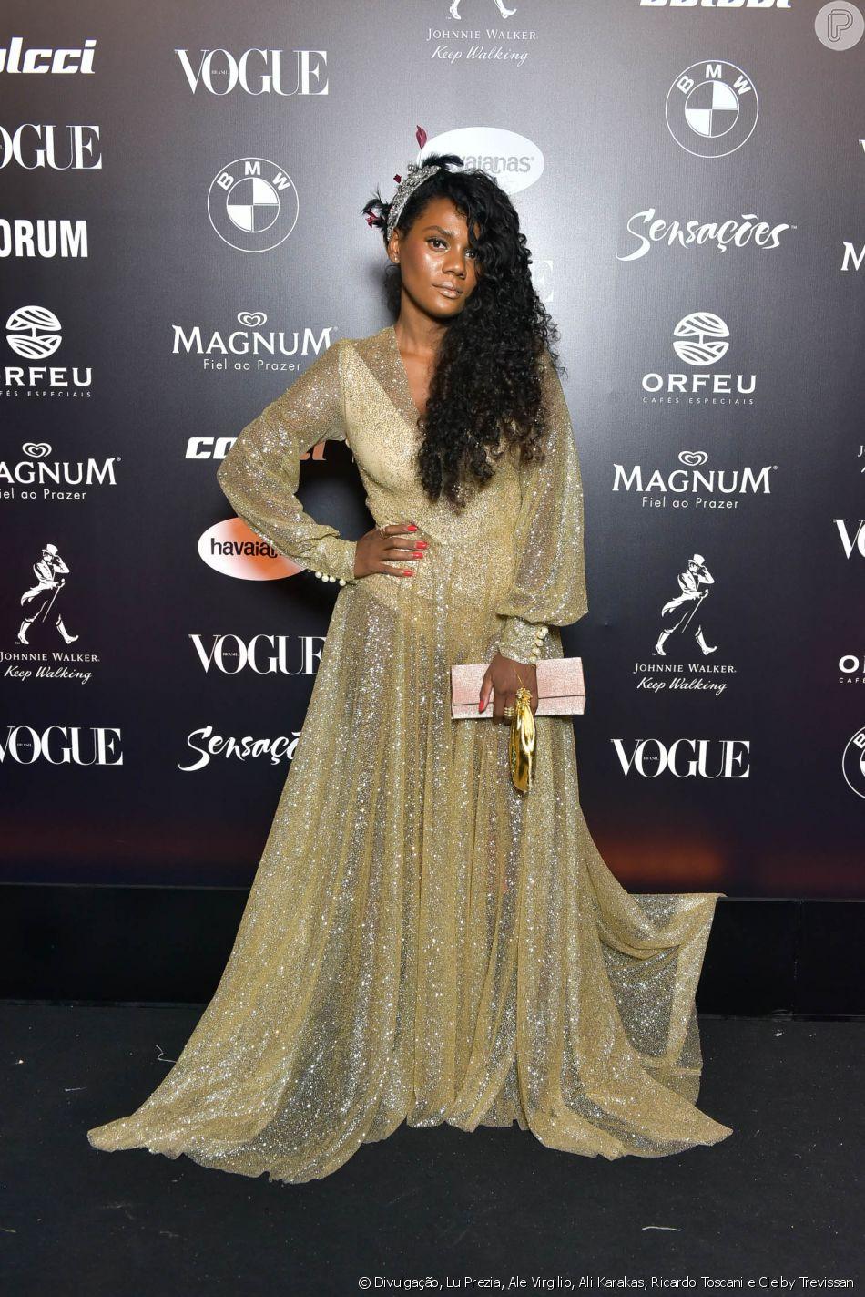 8f7dc62634161 Baile da Vogue  Camila Botelho de vestido dourado com transparência ...