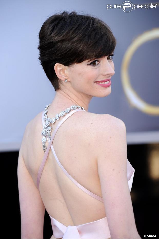 Anne Hathaway posa no red carpet com o colar para trás, que deu ainda mais charme ao look escolhido pela atriz, em 24 de fevereiro de 2013