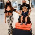 Filho de Isis Valverde deixa aeroporto sentado nas malas da família