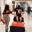 Filho de Isis Valverde nota paparazzo, olha para a atriz e gesticula