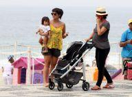 Grávida, Carolina Ferraz empurra carrinho de bebê da amiga em passeio na praia