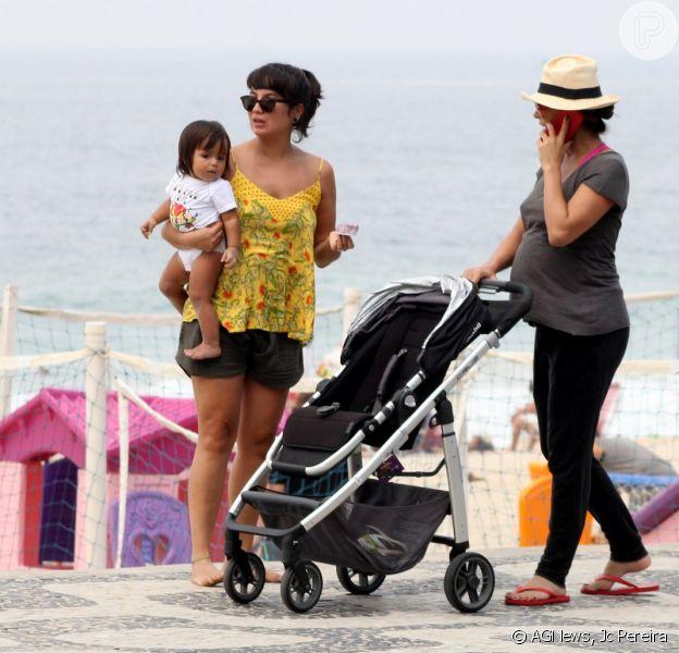 Grávida, Carolina Ferraz empurra carrinho de bebê da amiga durante caminhada na orla da praia do Leblon, no Rio, neste domingo 15 de março de 2015