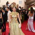 Tabitha Simmons escolheu um vestido longo dourado e destacou o look com um adereço de cabeça