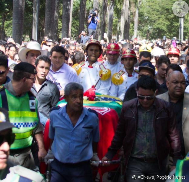 Corpo de Cristiano Araújo chega ao Cemitério Jardim das Palmeiras coberto pelas bandeiras do Brasil e do Villa Nova, time de coração do cantor