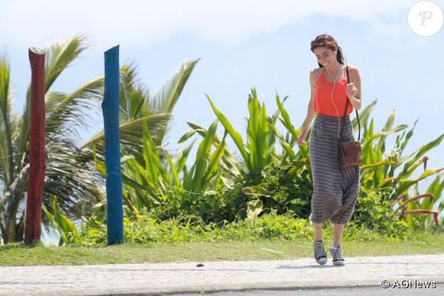 Maria Casadevall aparece bem descontraída ouvindo música e dançando enquanto caminha