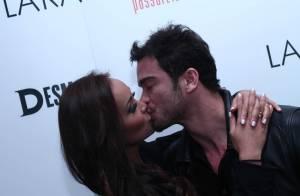 Sidney Sampaio e a noiva, Carol Nakamura, trocam beijos em evento de moda
