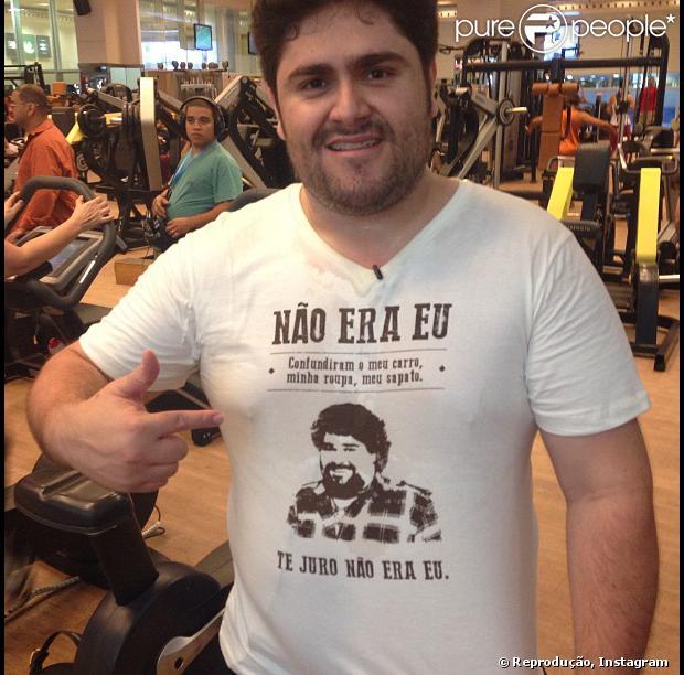 César Menotti posa em uma academia com o rosto do parceiro de dupla, Fabiano, estampado