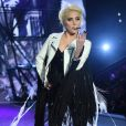 Lady Gaga investiu em um macacão preto justo ao corpo e  completou o look com uma jaqueta com franjas brancas
