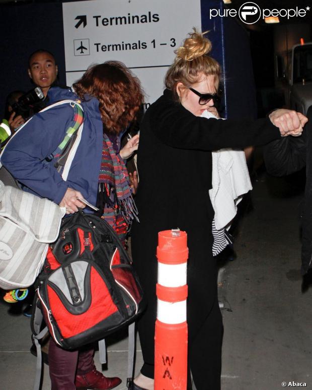 Adele esconde rosto do filho durante desembarque no aeroporto de Los Angeles, nos Estados Unidos, onde chegou para a festa da premiação do Globo de Ouro, em 11 de janeiro de 2013
