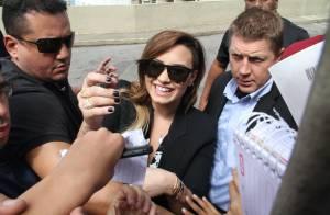 Demi Lovato distribui autógrafos para fãs em porta de hotel no Rio de Janeiro