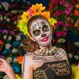 A caveira mexicana alegre pode ser criada com babados no vestido preto, plumas e acessórios exuberantes