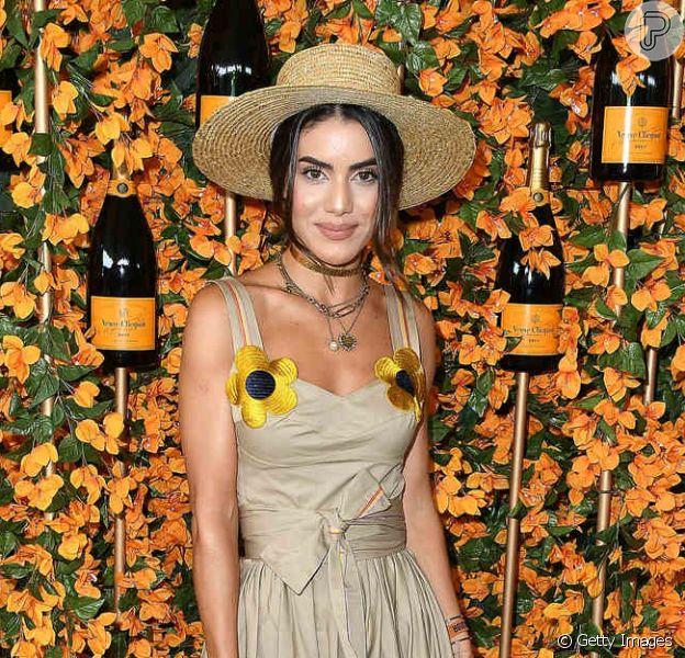 Detalhe floral: a blogueira brasileira Camila Coelho escolheu um vestido longo e liso com duas flores amarelas fixadas na alça do vestido