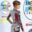 A combinação de vestido curto metalizado e bota over knee com o mesmo efeito foi a escolha de Taylor Swift para o AMA 2018
