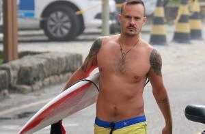 Sem camisa, Paulinho Vilhena exibe corpo em forma e surfa em praia carioca
