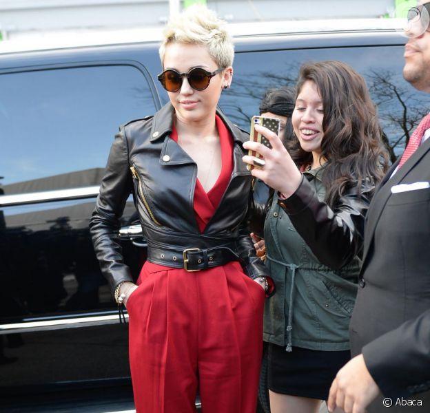 Miley Cyrus chega ao Fahion Show em Nova York, nos EUA, em 13 de fevereiro de 2013. Ela usa um macacão Rachel Zoe com uma jaqueta Moschino, óculos de sol Quay Eyeware Australia e sapatos Jean-Michel Cazabat