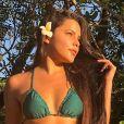 Emilly Araújo estilizou o cabelo solto na praia com uma flor na lateral dos fios