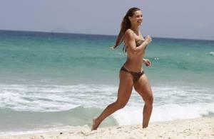 Carolina Dieckmann, com biquíni comportado de oncinha, curte praia no Rio