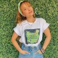 Larissa Manoela posa com t-shirt de estampa divertida com short jeans clochard. A atriz elege faixa de cabelo para combinar com o visual