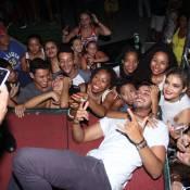 Rodrigo Simas se joga no chão para tirar foto com fãs na quadra da Grande Rio