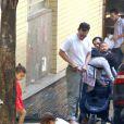 Camila Alves arruma carrinho de bebê do filho enquanto os outro dois brincam na calçada