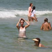 Juliana Didone mergulha de roupa no mar da praia da Barra da Tijuca, no RJ