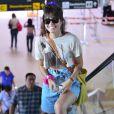Maria Casadevall sorri ao ver fotógrafo em aeroporto