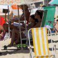 Cláudia Abreu se protege do sol e curte leitura com o filho em praia do Rio de Janeiro