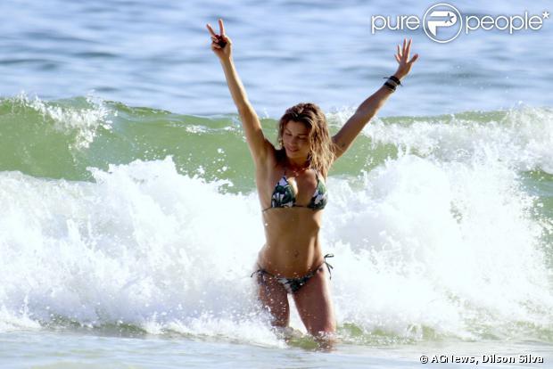 Grazi sai do mar e corre na areia para se vestir. Antes de deixar a praia a atriz atendeu ao pedido de fotos com fãs