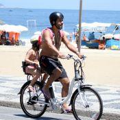 Marcos Palmeira leva a filha na garupa de bicicleta em orla de praia carioca