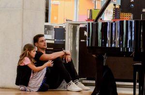Cauã Reymond e a filha se sentam no chão para ver pianista em shopping. Fotos!