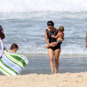Cláudia Abreu curte domingo de sol na praia com a família exibindo maiô discreto