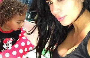 Kim Kardashian exibe seu decote e cachinhos da filha, North, com cara de sono