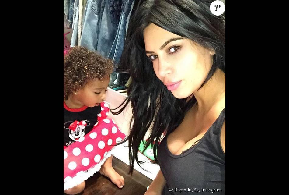 Kim Kardashian brindou seus seguidores com uma foto da filha, North, que aparece na foto com cara de sono e de cachinhos. Além da filha, socialite exibiu mais um de seus famosos decotes, nesta segunda, 28 de setembro de 2015