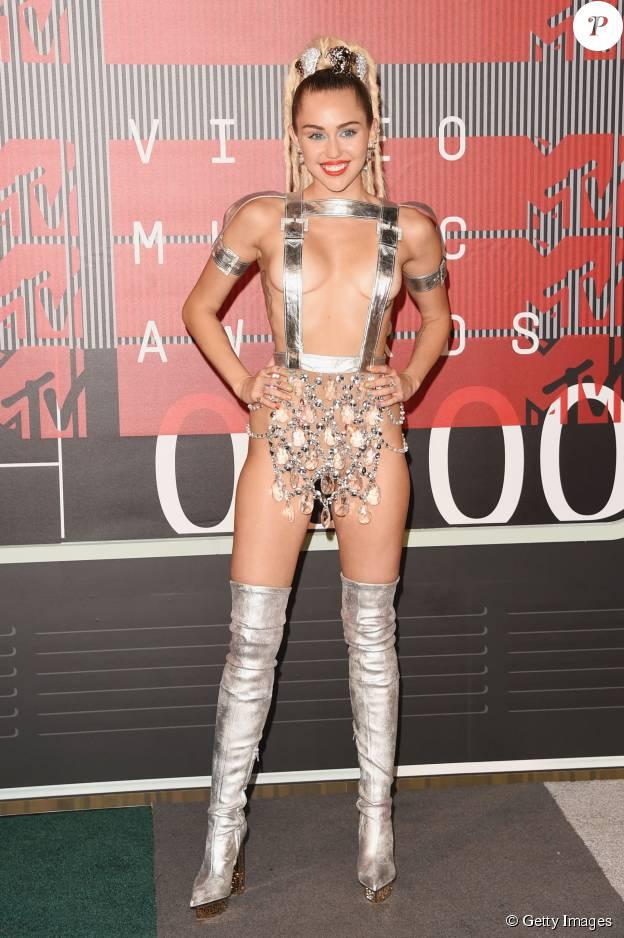 Miley Cyrus é mais uma famosa que adora ousar em seus looks. A popstar usou diversos figurinos para apresentar o Video Music Awards (VMA) 2015, como este da foto, composto por um suspensório prata, que tampava apenas seus mamilos, e uma tanga de material transparente