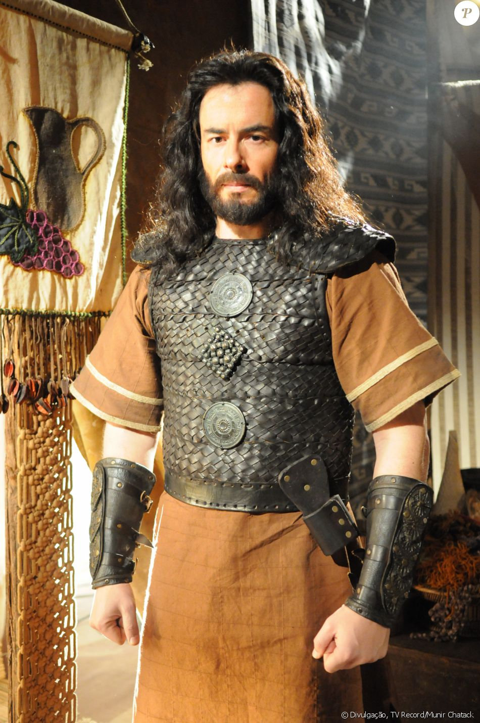 Eliéber (Felipe Folgosi) é quem ensina a irmã de criação, Aruna (Thais Melchior), a usar arco e flecha, na novela 'A Terra Prometida'