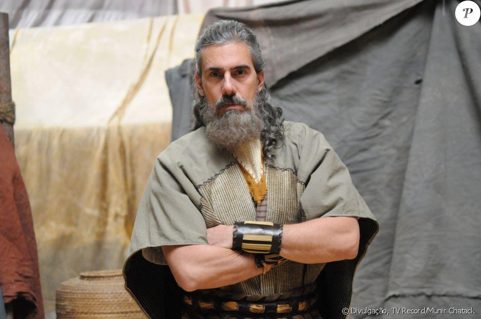 Quenaz (Zeca Carvalho) protege o filho, Otniel (Leonardo Miggiorin), diante das suas dificuldades de guerrear, na novela 'A Terra Prometida'