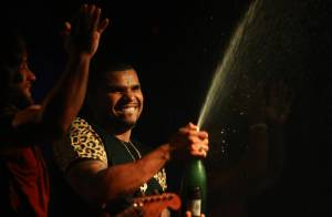 Naldo toma banho de champanhe e ganha flores de fãs em boate no Rio