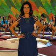 Fátima Bernardes   escolhe um vestido azul escuro com recortes na manga. Incrementando o look, a apresentadora opta por acessórios em verde, como o cintinho fino que marca a cintura e o maxicolar