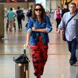 Anitta combinou jaqueta jeans, calça camuflada e bota de cano médio de verniz para viajar. Para completar a produção a cantora apostou em óculos de jatinho e mala grifada
