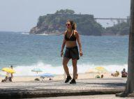 Adriana Esteves caminha de top e short em orla de praia. Fotos!